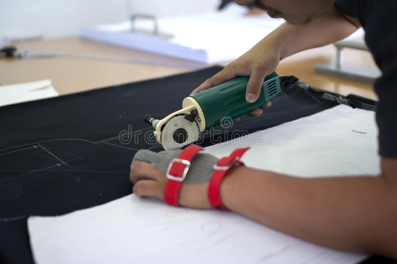 Male worker on a sewing manufacture uses electric cutting fabric machine with chain glove stock photo
