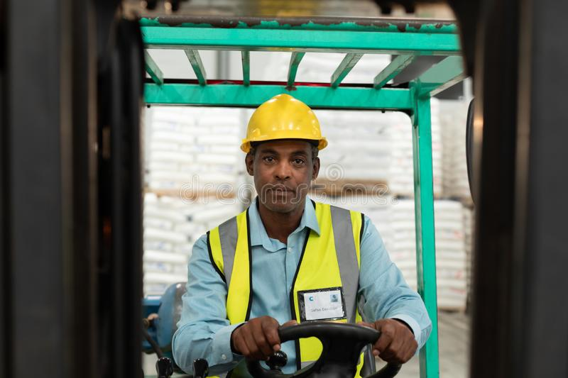 Male worker sitting in forklift and looking at camera in warehouse. Front view of male worker sitting in forklift and looking at camera in warehouse. This is a royalty free stock photography