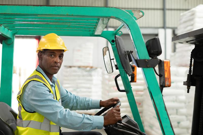 Male worker sitting in forklift and looking at camera in warehouse. Side view of male worker sitting in forklift and looking at camera in warehouse. This is a stock photography