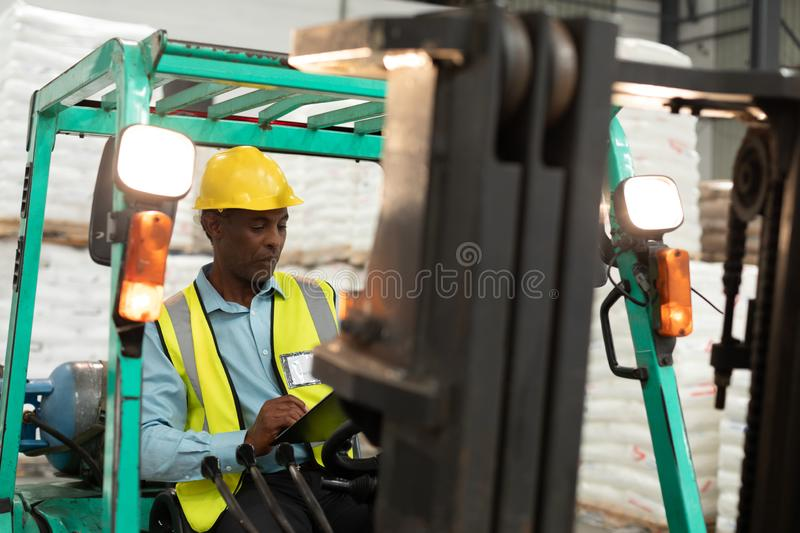 Male worker sitting in forklift and writing on clipboard in warehouse. Front view of male worker sitting in forklift and writing on clipboard in warehouse. This royalty free stock photography
