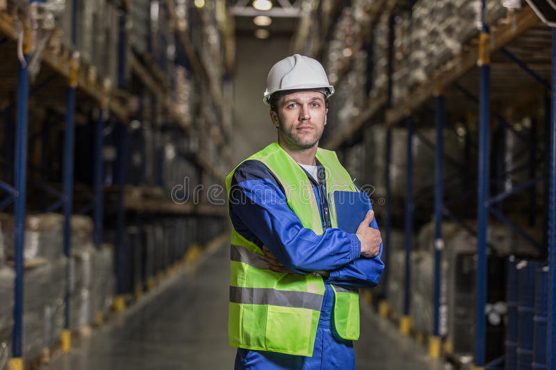 Male worker standing between selves with notebook stock photo