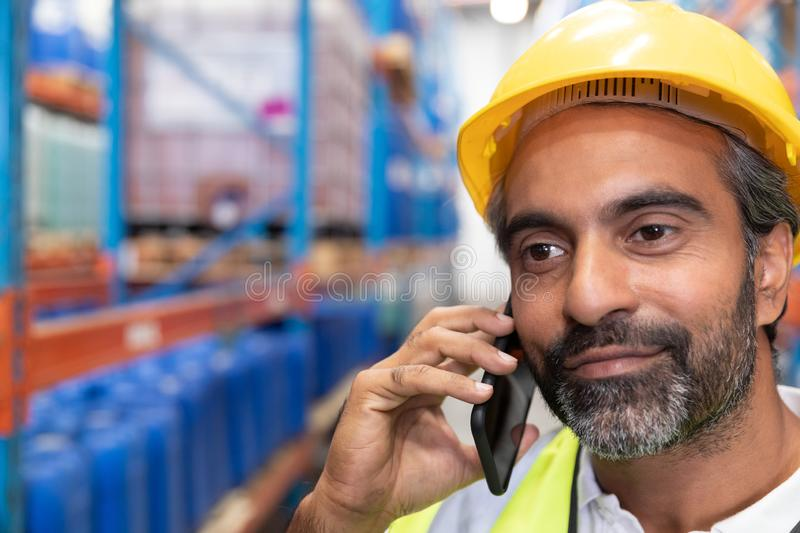 Male worker talking on mobile phone in warehouse. Close-up of male worker talking on mobile phone in warehouse. This is a freight transportation and distribution stock photography