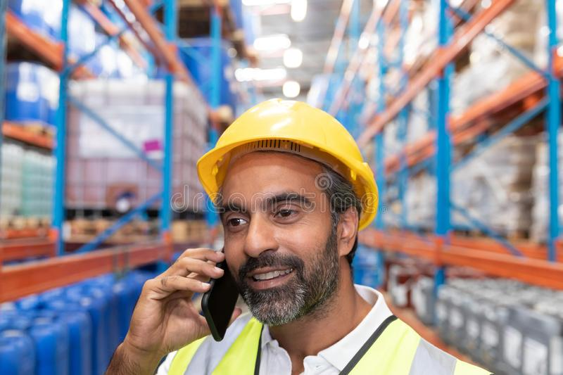 Male worker talking on mobile phone in warehouse. Close-up of male worker talking on mobile phone in warehouse. This is a freight transportation and distribution royalty free stock photo