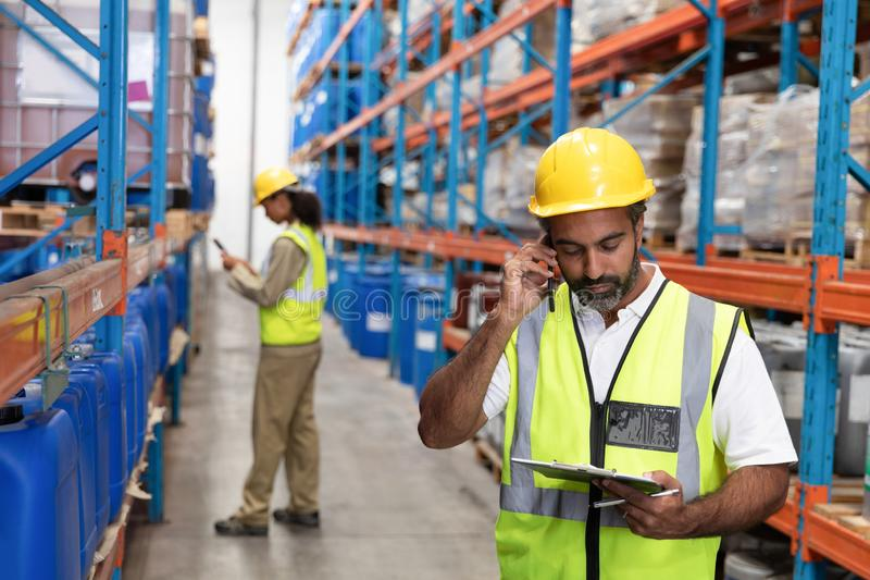 Male worker talking on mobile phone in warehouse. Front view of male worker talking on mobile phone in warehouse. This is a freight transportation and royalty free stock image