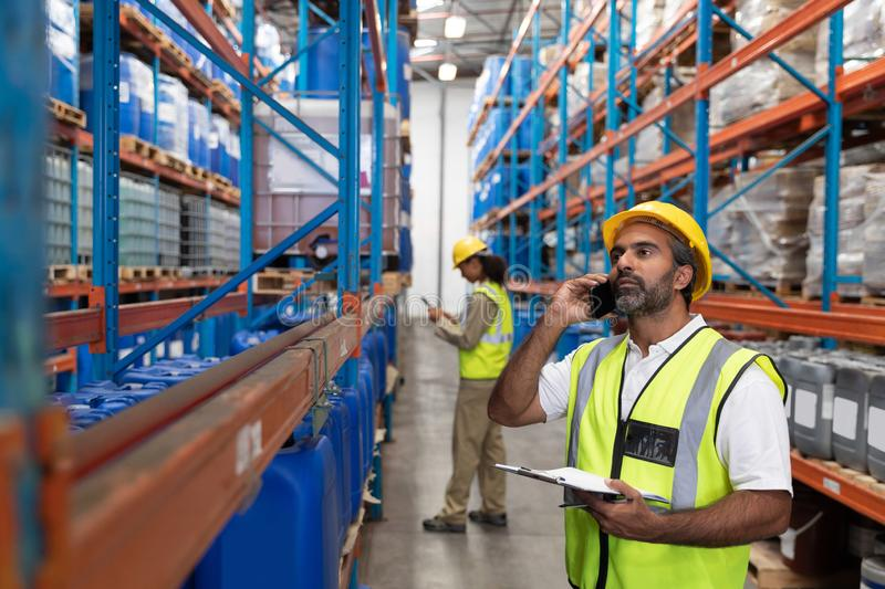 Male worker talking on mobile phone in warehouse. Front view of male worker talking on mobile phone in warehouse. This is a freight transportation and royalty free stock photography