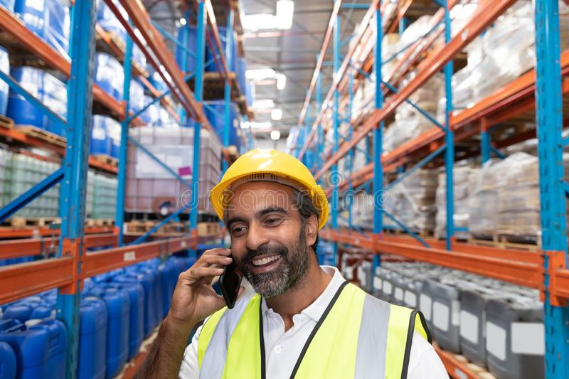 Male worker talking on mobile phone in warehouse. Happy male worker talking on mobile phone in warehouse. This is a freight transportation and distribution royalty free stock image