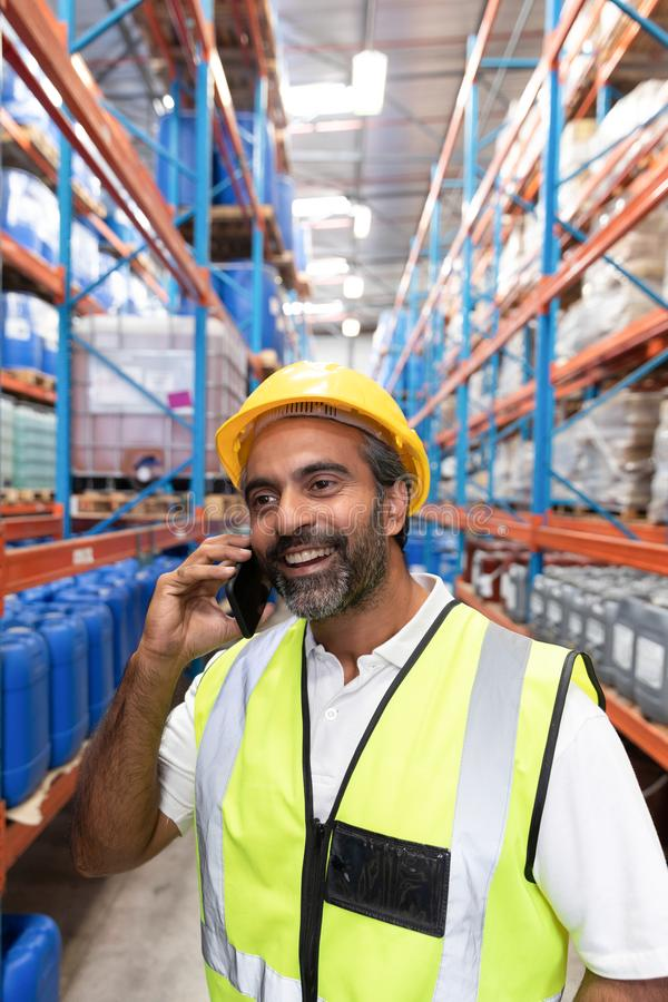 Male worker talking on mobile phone in warehouse. Happy male worker talking on mobile phone in warehouse. This is a freight transportation and distribution royalty free stock photos