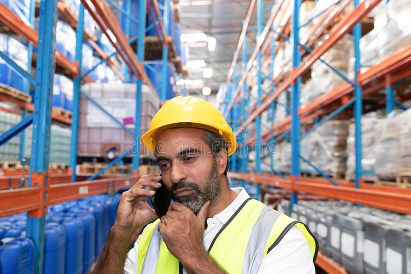 Male worker talking on mobile phone in warehouse. Thoughtful male worker talking on mobile phone in warehouse. This is a freight transportation and distribution royalty free stock photo