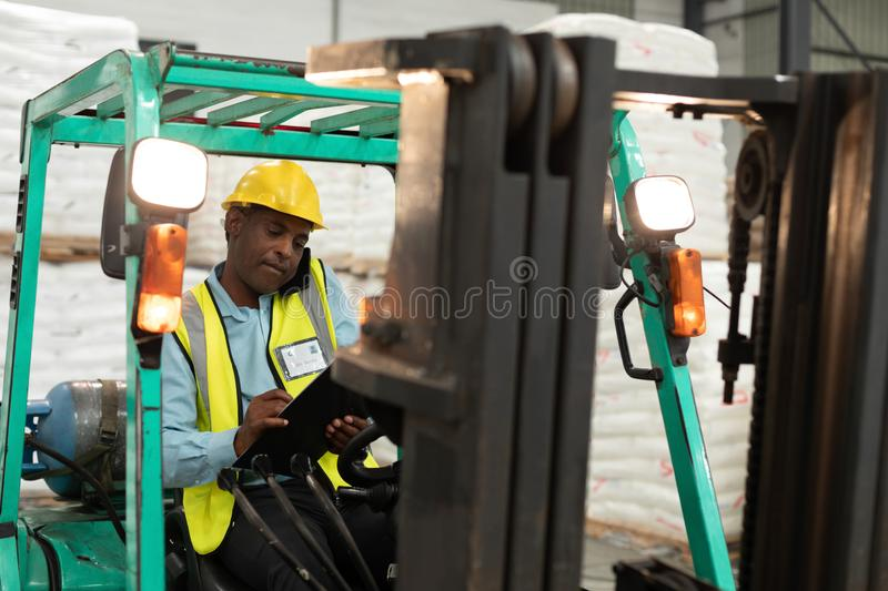 Male worker talking on mobile phone and writing on clipboard in forklift royalty free stock image