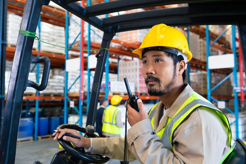 Male worker talking on walkie-talkie while driving forklift in warehouse stock photos