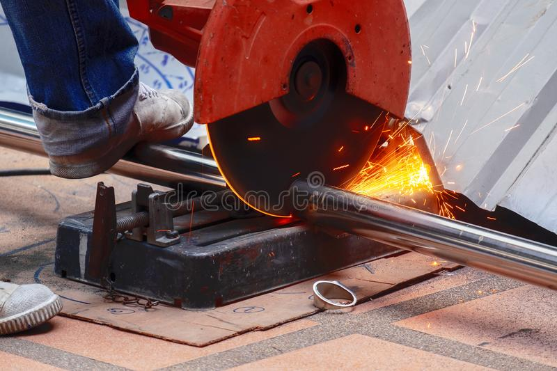 Male Worker Use Chop Saw to Cutting a Thick Stainless Steel Tube stock image