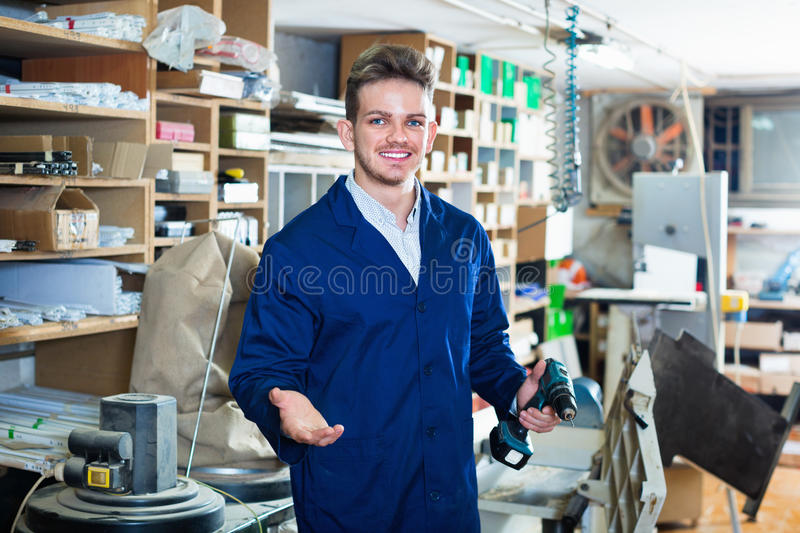 Male worker using drill for work at workshop stock photos