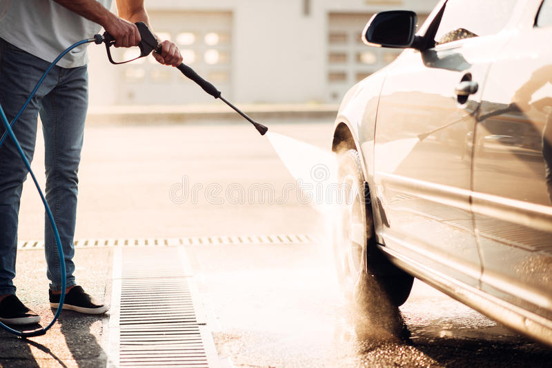 Male worker wash the car with high pressure washer royalty free stock image