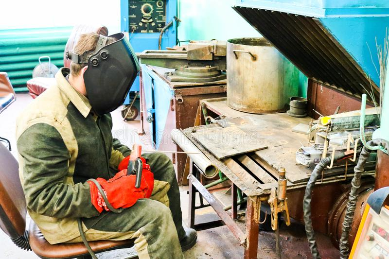 A male worker a welder in a protective mask welds a metal pipe at a welding station in a workshop at a metallurgical plant royalty free stock photo