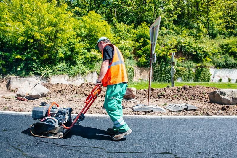 Male worker working with industrial hand tool asphalt posing stock photography