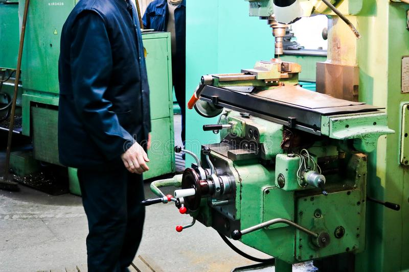 A male worker works on a larger metal iron locksmith lathe, equipment for repairs, metal work in a workshop at a metallurgical royalty free stock images