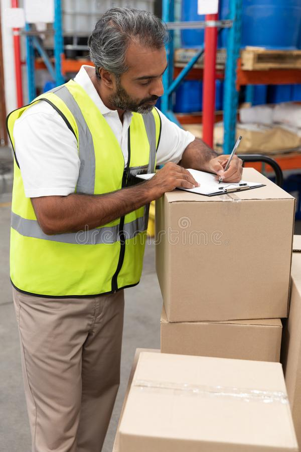 Male worker writing on clipboard in warehouse. Front view of male worker writing on clipboard in warehouse. This is a freight transportation and distribution royalty free stock photography