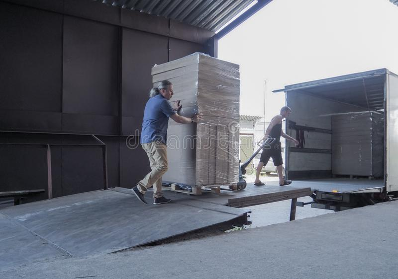 Truck loading and shipping. Male workers are loading the goods in cardboard boxes on a truck. royalty free stock images