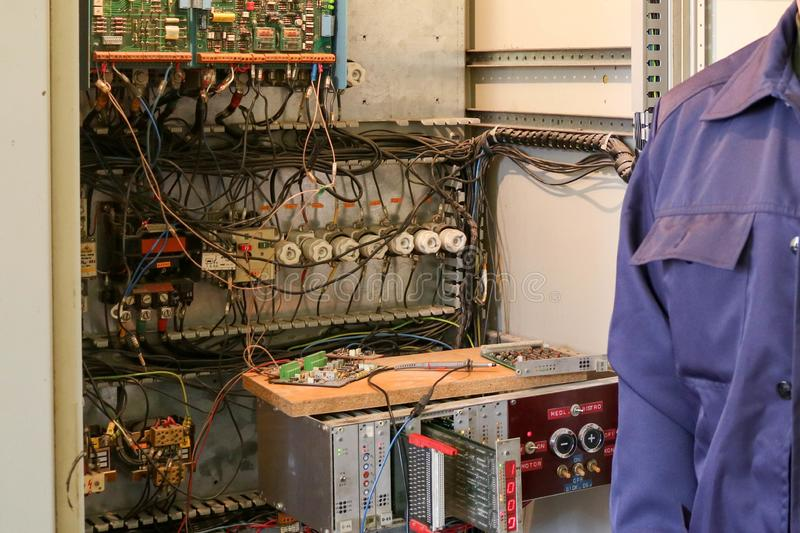 A male working electrician stands in front of an electrical panel with wires, transistors, fuses, electronics and switches.  royalty free stock photo