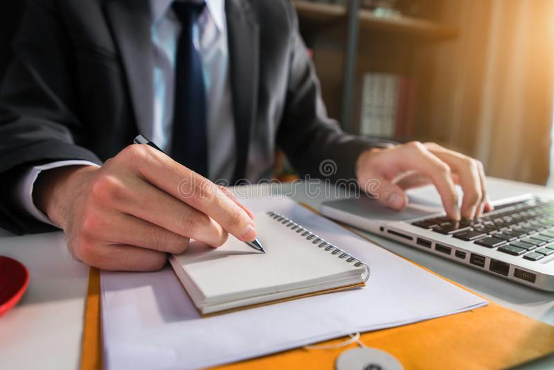 Male writes information businessman working on laptop computer. stock images