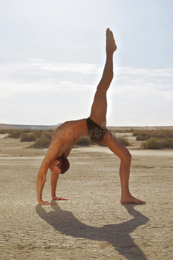 Male Yoga Pose. Young man performing Yoga pose in the desert stock photos