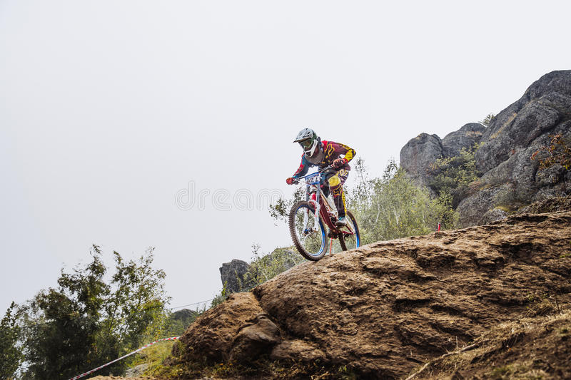 Male young driver athlete on bike at edge of cliff stock photos