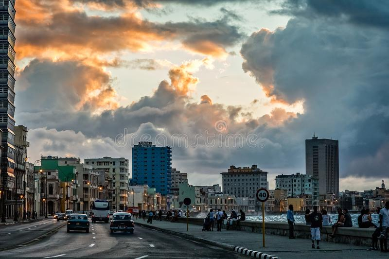 Malecon promenade street with walking people and road with traffic in the evening time with sunset clouds, Havana, Cuba stock photo