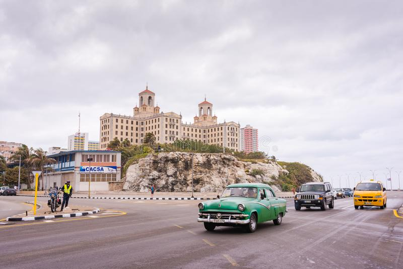 Malecon Road and Hotel Nacional de Cuba / National Hotel of Cuba. Havana, Cuba / March 21, 2016: Malecon - seawall - highway in front of hill topped by historic royalty free stock image