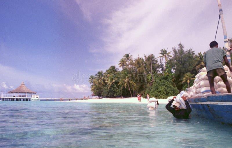 Maledives: los bolsos de la arena se descargan de un barco para proteger la isla contra nivel del mar de la sublevaci?n foto de archivo