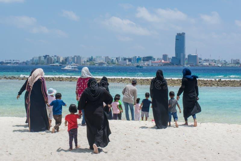 Maledivische Frauen und Kinder, die in Richtung zum Ozean am tropischen Strand gehen lizenzfreies stockbild