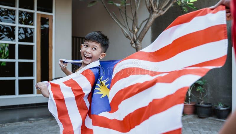 Maleis jong geitje met vlag het lopen stock fotografie