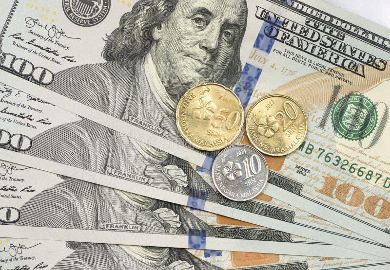 Maleis Ringgit muntstuk bovenop dollarrekeningen stock afbeelding