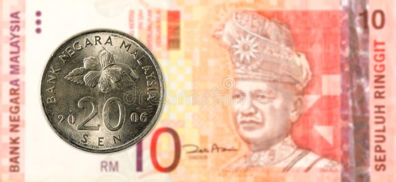 20 Maleis sen muntstuk tegen Maleis ringgit 10 bankbiljet stock foto