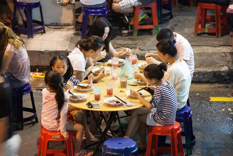 Maleise familie die bij de boxen van het straatvoedsel, Penang dineren stock foto