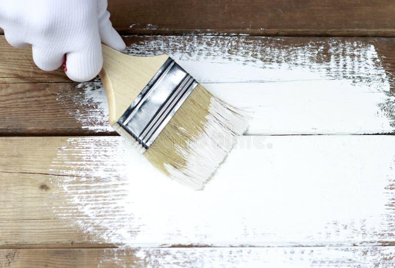 Malen einer Holzoberfläche mit weißer Farbe, eine behandschuhte Hand, die einen Pinsel hält lizenzfreie stockbilder