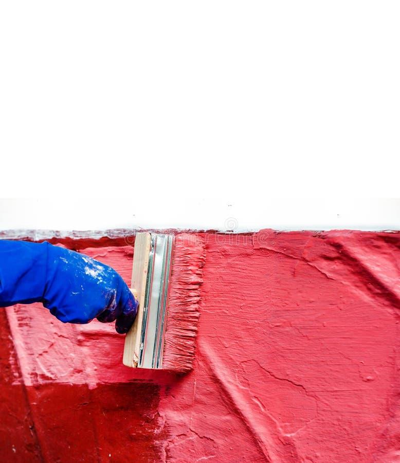 Malen Sie die Wand im Rot mit einem gro?en breiten Pinsel lizenzfreie stockfotos