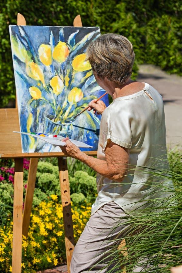 Malende Blumen der älteren Frau auf Segeltuch im Garten während des sonnigen Tages stockfotos