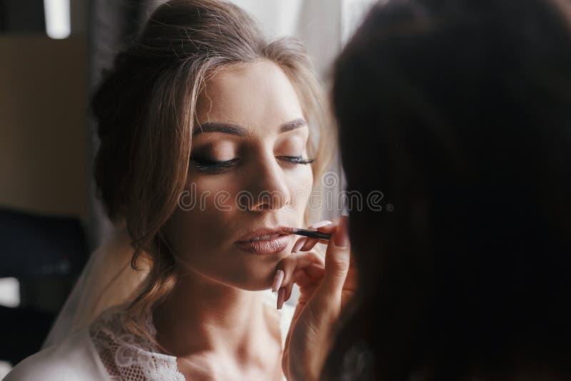 Malende Lippen des Maskenbildners mit nacktem Lippenstift auf dem Gesicht c der Braut lizenzfreies stockfoto