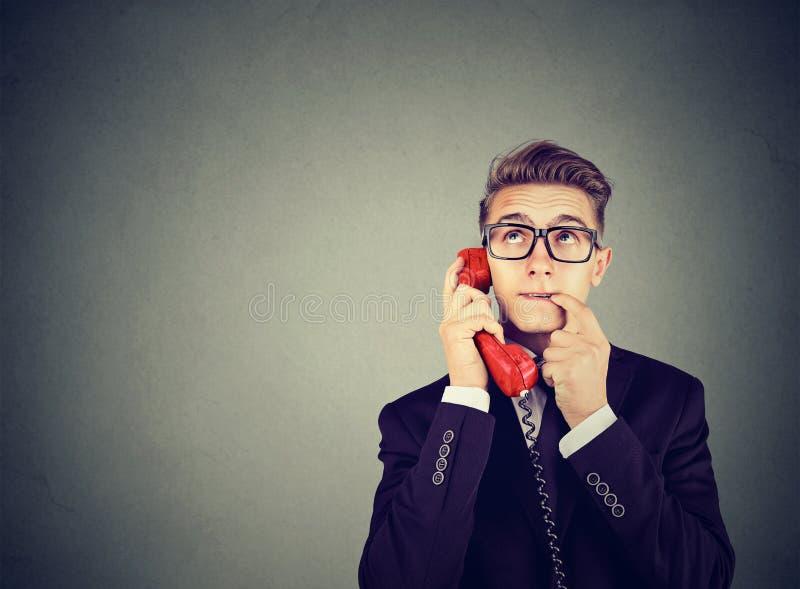 Malentendu et appel éloigné L'homme confus inquiété par renversement parlant à un téléphone a beaucoup de questions photo stock
