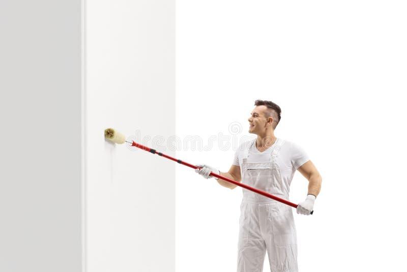Maler, der eine Wand mit einer Rolle malt lizenzfreies stockfoto