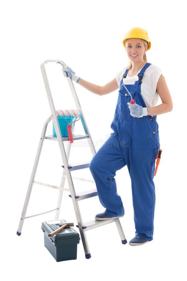 Maler der jungen Frau in der blauen Erbaueruniform mit Leiter und Werkzeug lizenzfreie stockbilder