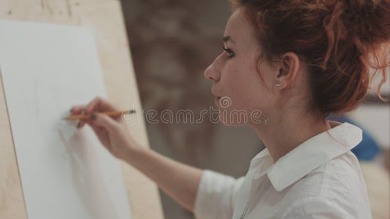 Maler der jungen Frau, der Skizzen auf leerem Segeltuch in der Künstlerwerkstatt macht lizenzfreies stockbild