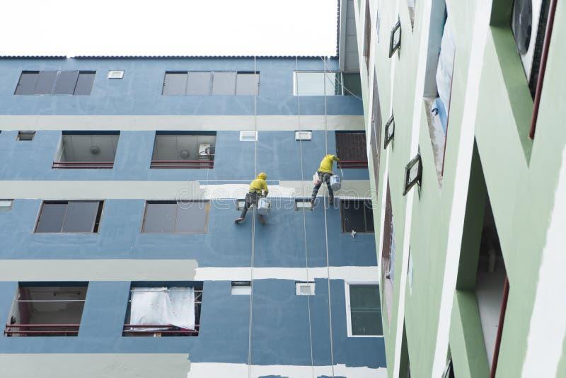 Maler, die an der Rolle, malende Farbe auf Gebäudewand hängen lizenzfreies stockbild