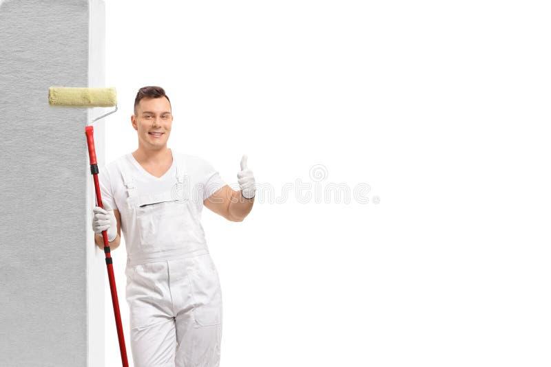 Maler mit einer Farbenrolle, die an der Wand sich lehnt und einen Daumen herauf Zeichen herstellt stockfoto