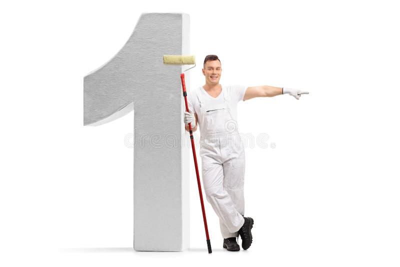 Maler mit einer Farbenrolle, die an einer Nummer Eins-Zahl sich lehnt stockbild