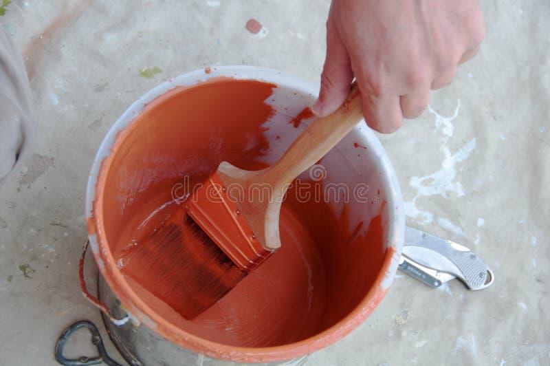 Maler wendet orange Lack am Pinsel vom Eimer an stockfotografie