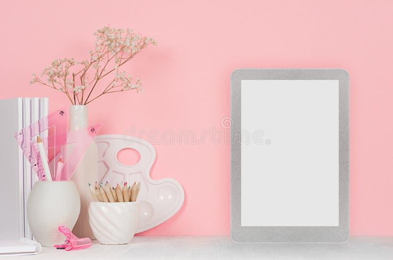 Malerarbeitsplatz - silberne Notentablette mit leerem Bildschirm, weißes Briefpapier, Palette, Bleistifte auf weichem rosa Hinter stockbilder