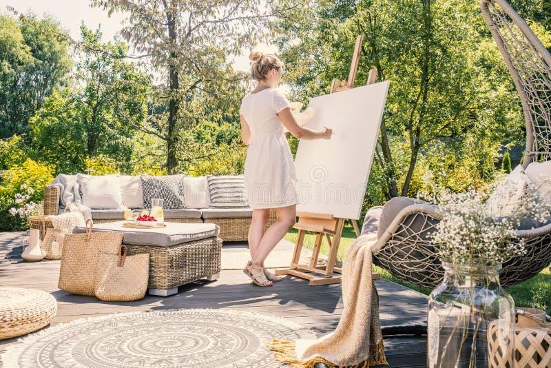 Malerei der jungen Frau auf einem weißen Segeltuch auf einer sonnigen Terrasse mit g stockfotografie