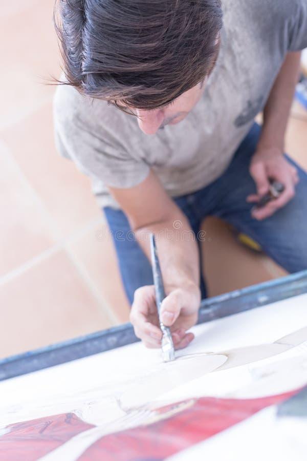 Malerei des jungen Mannes auf Segeltuch - Malereisitzung lizenzfreies stockbild