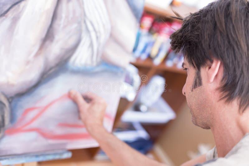 Malerei des jungen Mannes mit Kreide auf Segeltuch - Malereisitzung lizenzfreies stockfoto